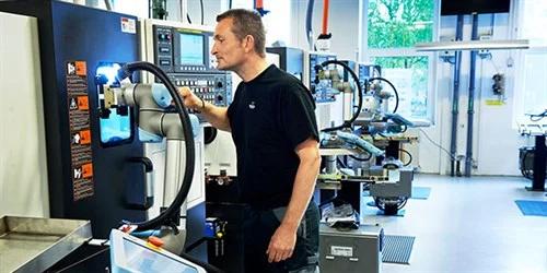 """Homem trabalhando em colaboração com máquina, no artigo """"Repensando a relação homem x máquina"""""""